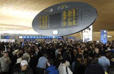 Travelers crowd in front of the Air France check-in counters at Roissy-Charles-de-Gaulle Airport north of Paris